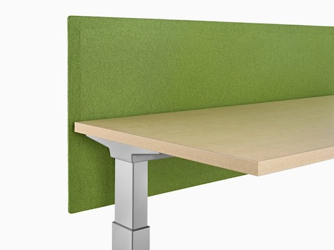 A green privacy screen attached to the back of a sit-to-stand desk.