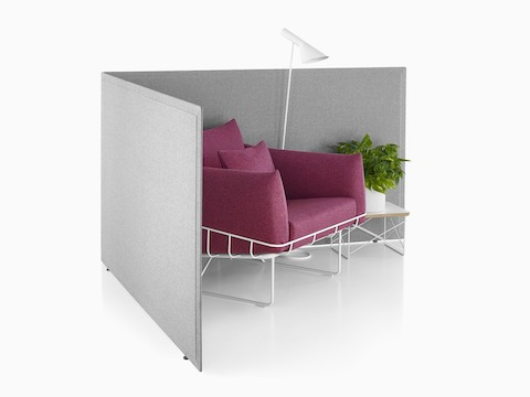 Light gray privacy screens define a partially enclosed solo work area featuring a magenta Wireframe lounge chair.