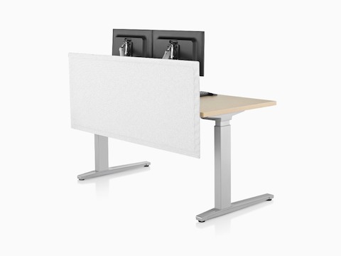 A white privacy screen attached to the back of a sit-to-stand desk supporting two monitors.