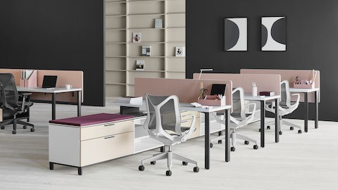 A Canvas Storage workstation in light wood with pink screens and light grey Cosm office chairs.