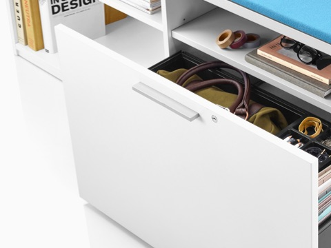 Close view of a white Herman Miller storage unit containing personal items and reference materials.