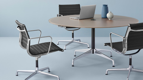 A round Eames Table surrounded by three Eames Aluminum Group Chairs. Select to go to the Eames Tables product page.