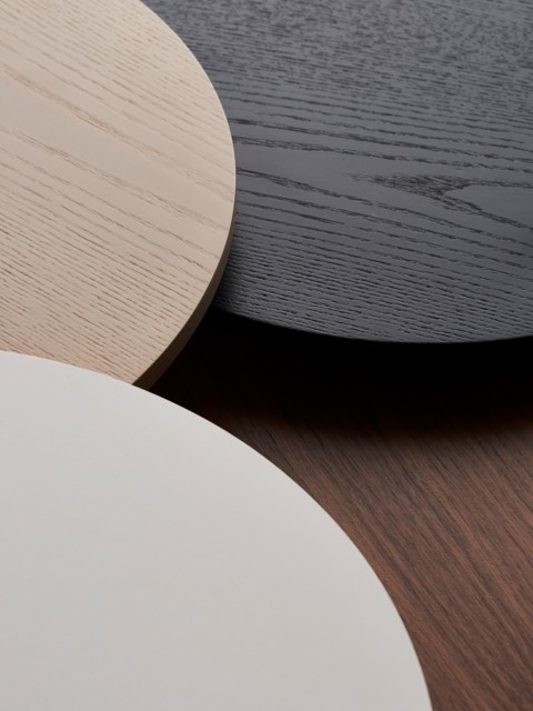 Overhead view of three overlapping round table tops in white, tan, and black.