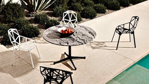 Overhead view of a stone-top Eames outdoor table next to a pool. Select to go to our outdoor tables pages.