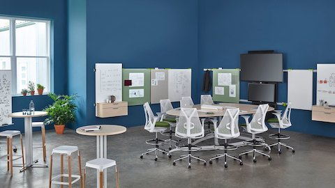 Sayl office chairs surround an Exclave table in an open collaboration space.  Select to go to the Exclave product page.