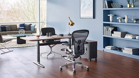 A black Aeron office chair paired with an Atlas Office Landscape desk in a private office with lounge seating and a window wall. Select to go to our private office page.