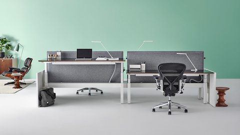 A Renew Link sit-to-stand benching system with gray divider screens and Aeron chairs. Select to go to our height-adjustable products page.