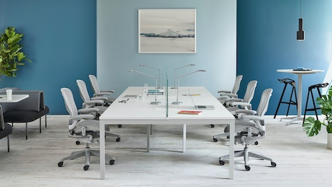A bright work environment with six orange Mirra 2 office chairs on either side of a shared, rectangular Canvas Beam surface. Select to go to our benching page.