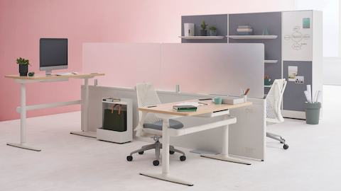 Two Catena Office Landscape workstations with white legs, a light wood surface and glass add-on screens accompanied by Sayl Chairs. Port Storage System is featured in the background.