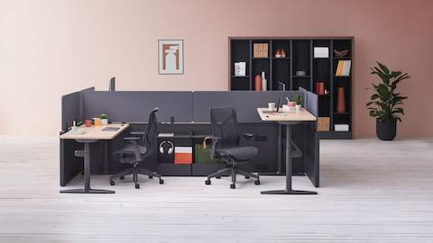 Catena Office Landscape workstations with light wood surfaces and grey fabric screens, accompanied by Ode integrated lighting and black Cosm chairs. Port Storage System is featured in the background.