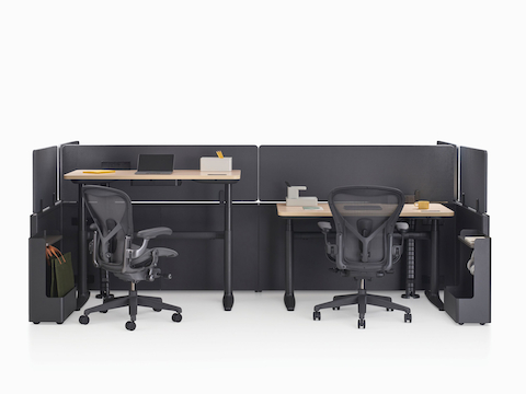 Catena Office Landscape workstations with light wood surfaces, black panels, and Ode integrated lighting. Two black Aeron Chairs accompany the workstations.