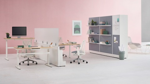 Catena Office Landscape workstations with white legs, light wood surfaced, and glass add-on screens accompanied by Sayl Chairs. Port Storage System is featured in the background.