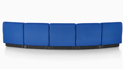 Five blue Chadwick Modular Seating modules arranged to form a gentle curve, viewed from the rear to show the upholstered back.