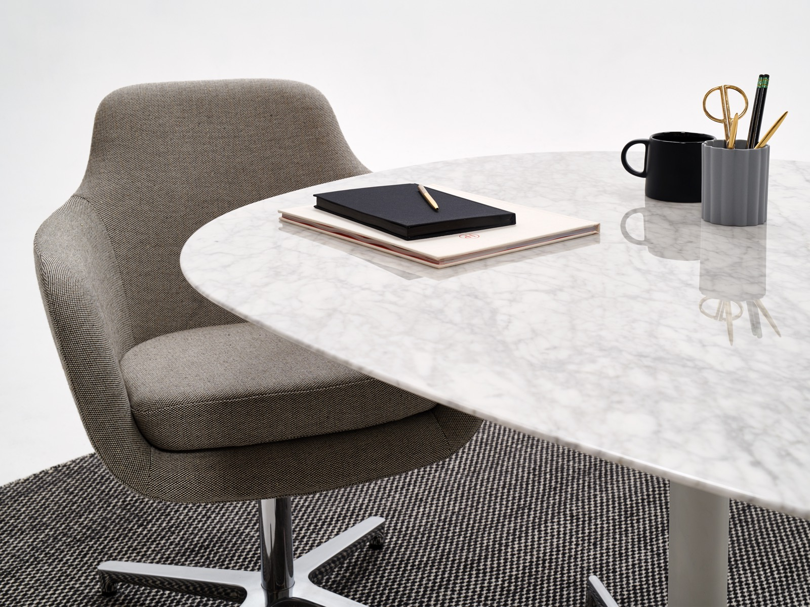 A white marble Civic Table with a grey Saiba office chair.