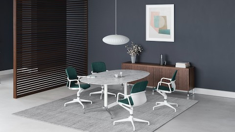 Four green and white Keyn chairs are grouped around a white marble Civic Table. A walnut screen divides the room with a standing height Civic Table positioned by a window.
