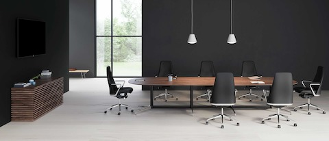 A large oval Civic Table with a walnut surface accompanied by 7 black leather Taper chairs.