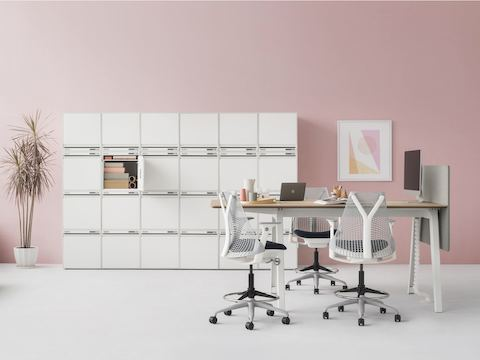 A CKL six pieces width by four pieces high of small locker in total 24 pieces combine as locker wall along with pink wall and a high Optimis table with four Setu stools.