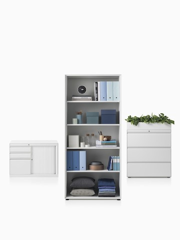 A CK8 right-hand return cabinet with shutter door compartment, CK8 open shelf high cabinet filled with stored items and CK8 three-high lateral filing mid-height cabinet with planter on top. Select to go to the CK Storage product page.