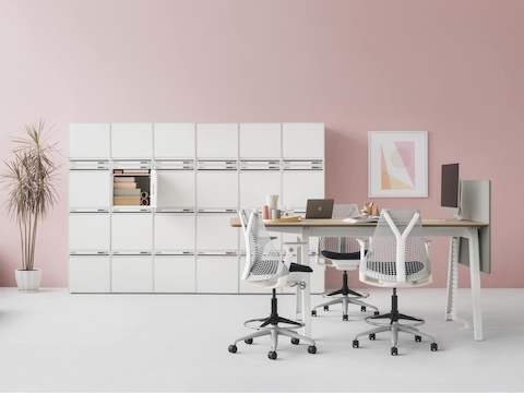 CKL six pieces width x four pieces high of small locker in total 24 pieces combine as locker wall along pink wall. A high Optimis table at the front with four Setu stools.