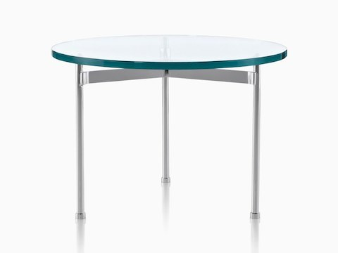 A glass-top Claw Table with a round surface and three metal legs.