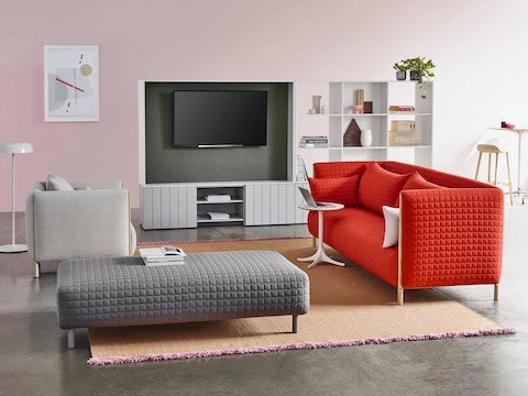 A casual work area with a red ColourForm sofa and a light gray ColourForm lounge chair and ottoman.