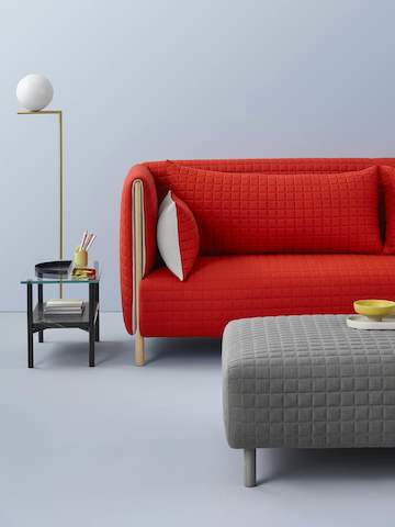 Partial views of a red ColourForm sofa and gray ColourForm ottoman.