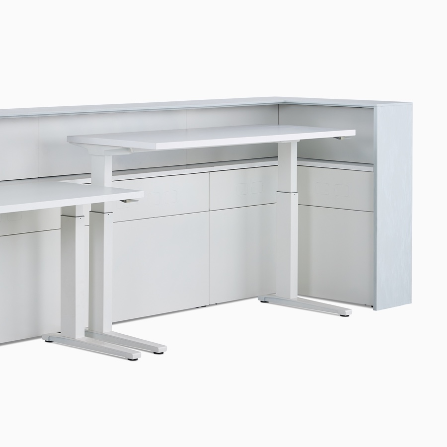 Two white Renew Sit-to-Stand Tables at differing heights tucked within the interior of a Commend Nurses Station.
