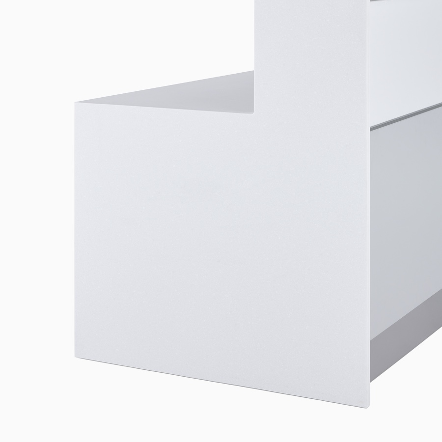 A close-up view of the white Corian full end panel with white laminate tops and white and gray fronts on a forty two inch high prefab Commend Nurses Station.