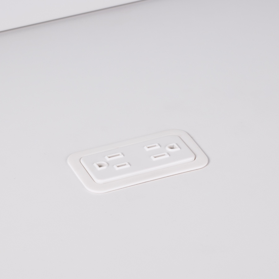 A close-up view of Logic Mini with two power outlets integrated into the top of a white laminate work surface.