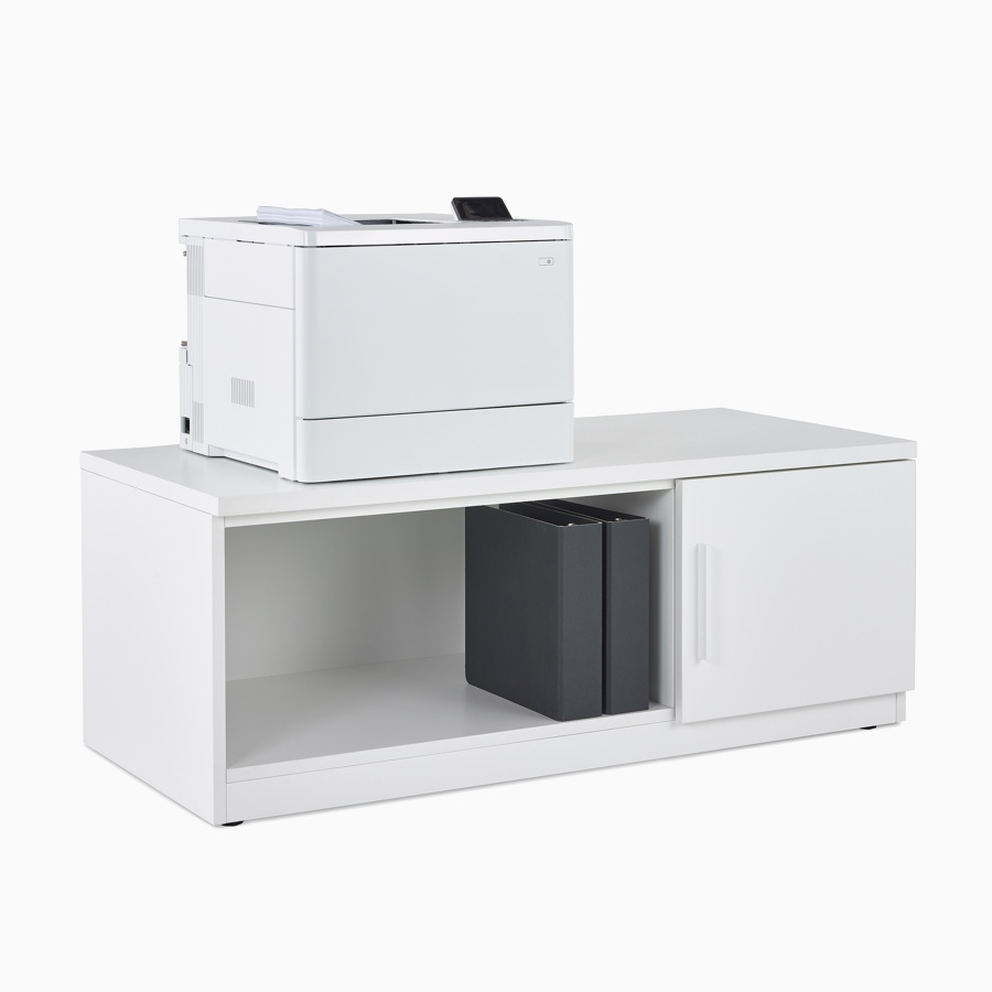 Mora System's printer storage with two cubbies, one open with two black binders and one closed, with a printer atop the storage.