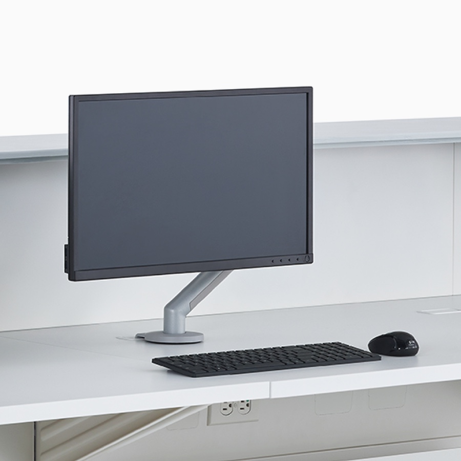 A close-up view of a Flo Monitor Arm with a screen on a prefab Commend Nurses Station white work surface.