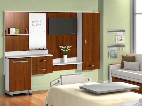 Compass System modular healthcare components in a patient room with a bed and sleeper sofa.