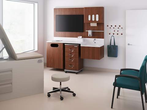 An exam room featuring a dark wood laminate Compass System and a blue stool on casters.