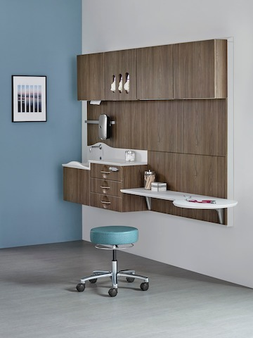 A telemedicine consultation exam room with Compass casework in an ash wood finish, with Florabella lounge seating in a light gray upholstery and Florabella occasional table in oak.