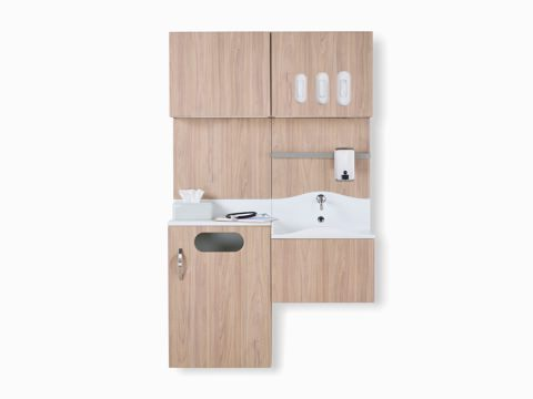 Front view of Compass System casework wall unit in a medium elm wood laminate finish with integrated waste receptacle, white solid surface sink, and upper storage for gloves.