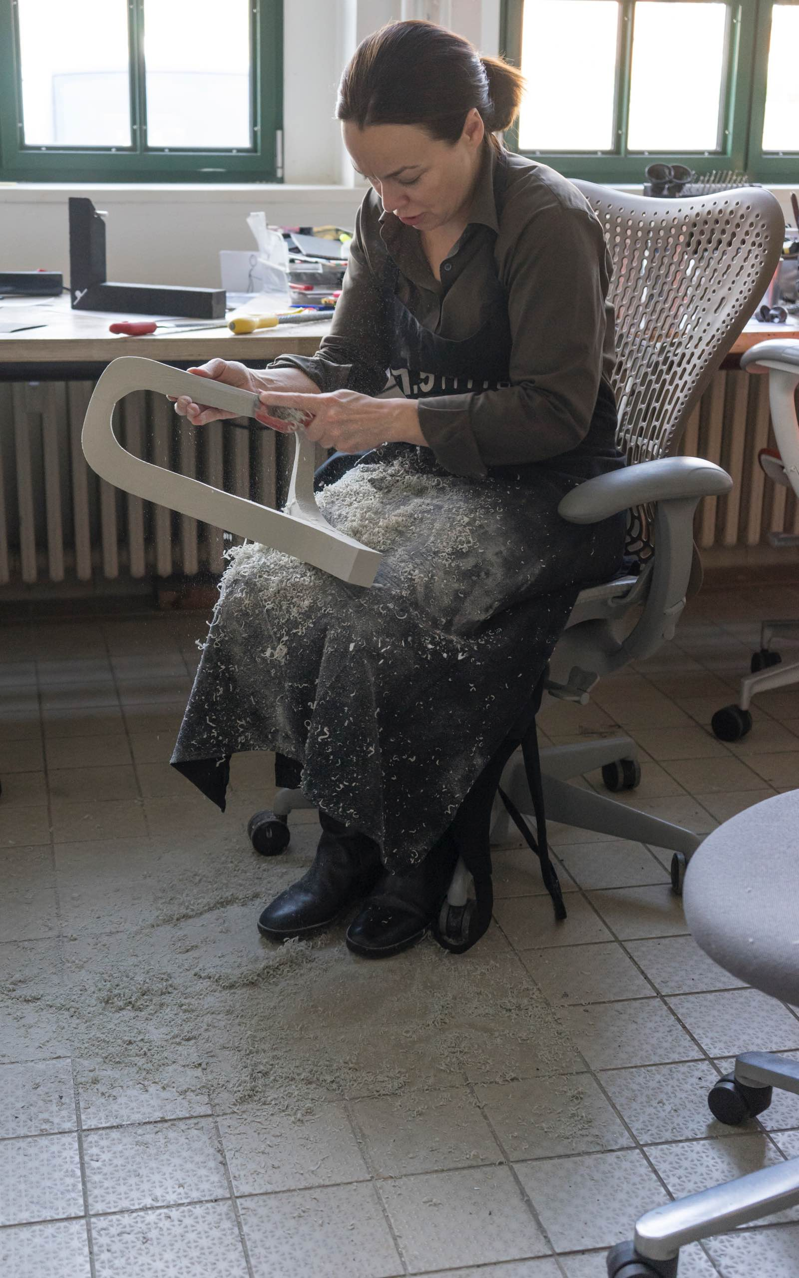 A member of Studio 7.5 shaves down material to make a model during the development of the Cosm Chair.