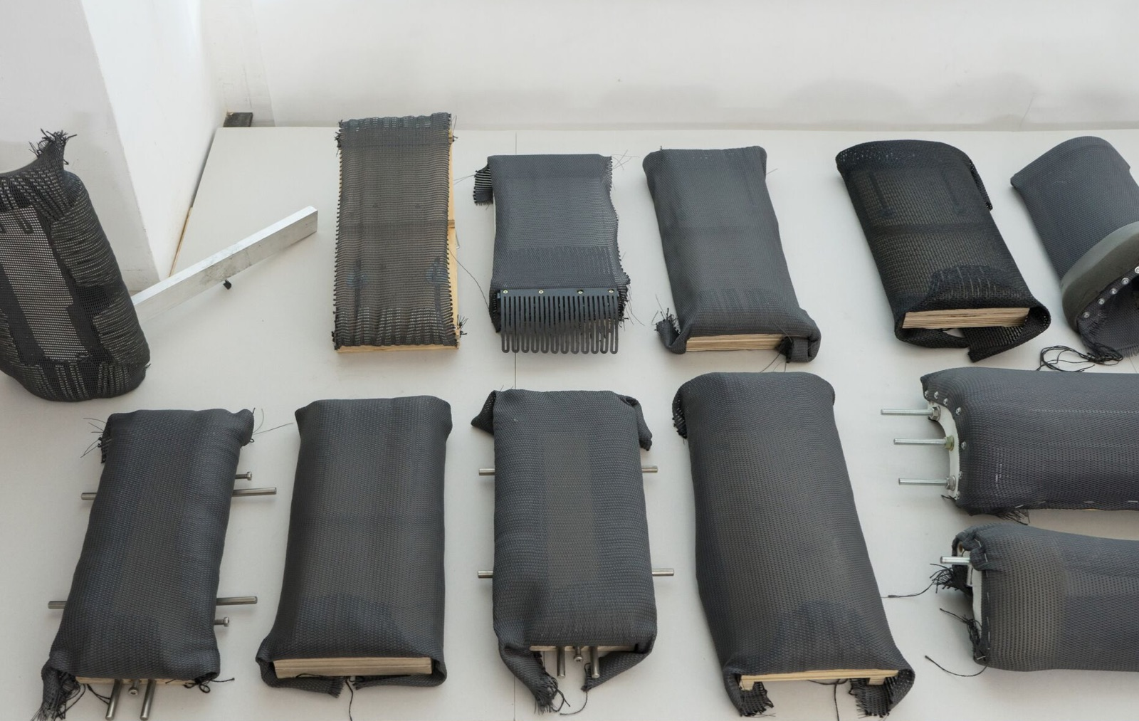 A variety of frames used to test suspension materials for Cosm Chairs sit on the floor or lean against a wall.
