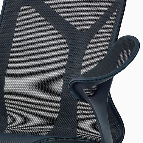 A close up of a Nightfall navy blue Cosm chair with leaf arms.