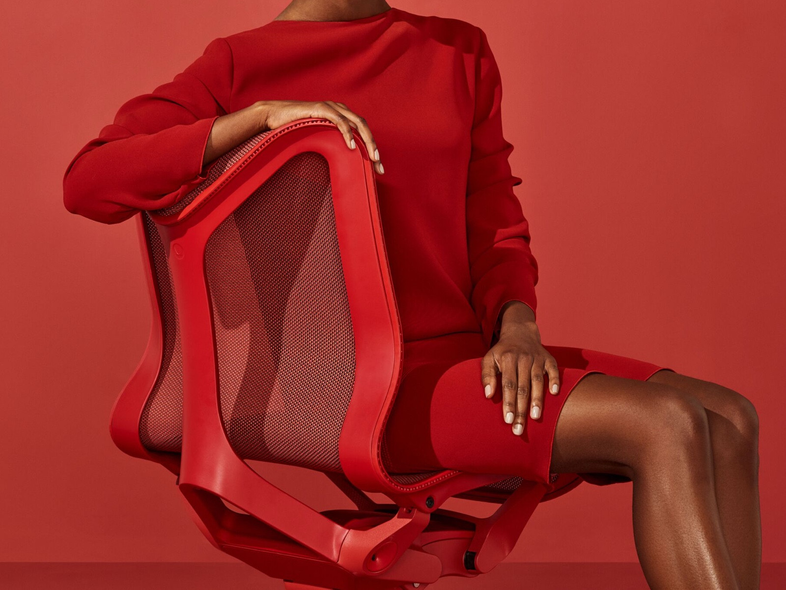 A woman in a red dress sits in a low-back Cosm Chair in Canyon red.