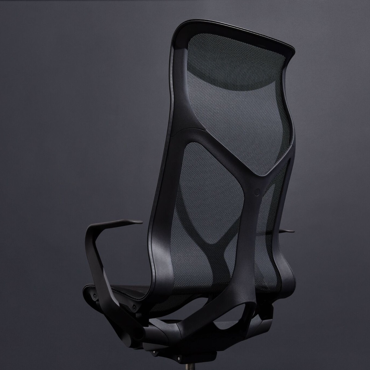 A Graphite dark grey Cosm high-back ergonomic desk chair with fixed arms on a dark grey background.