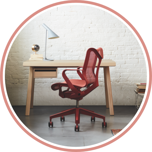 A small office with a Canyon red Cosm low-back chair in front of a Distil desk in ash. Select to start shopping for Cosm for your home or small business.