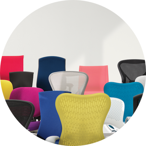 A variety Herman Miller work chairs in different colors grouped together.
