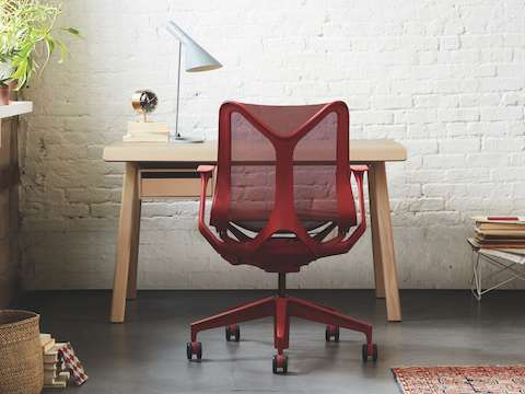 A small office with a Canyon red Cosm low-back chair in front of a Distil desk in ash.