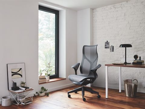 A small office with a Graphite gray Cosm high-back chair next to a rectangular Everywhere table with a walnut top and white legs.