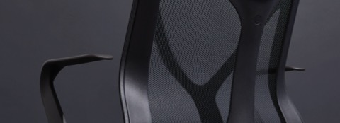 A close up of a Graphite gray Cosm Chair with fixed arms on a gray background.