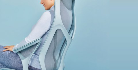 A woman wearing blue linen pants and a light blue sweater reclines in a Glacier light blue Cosm high-back ergonomic office chair.