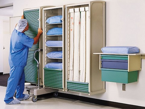A healthcare worker positions a movable Co/Struc locker on a wall rail.