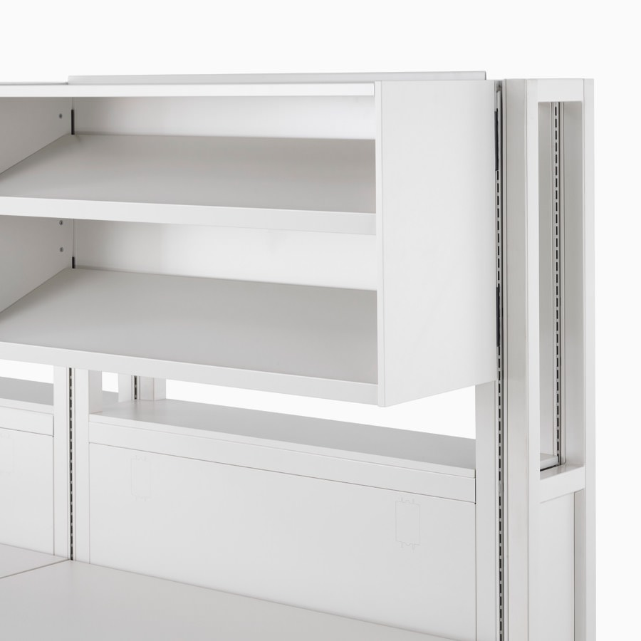 Detail of soft white Co/Struc System frame module with upper storage unit with display shelves.