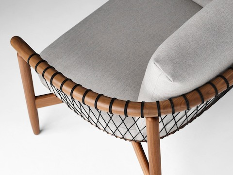 A detailed shot of a Crosshatch Settee with a walnut frame, black cords and light neutral fabric.