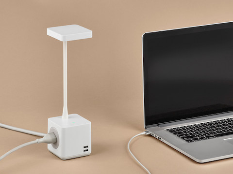 A compact Cubert Personal Light charges an open notebook computer.